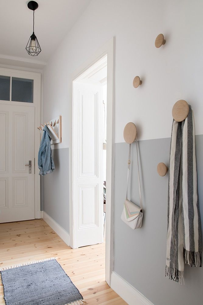 Beautiful modern and Scandinavian inspired entryway with a half-painted wall and...