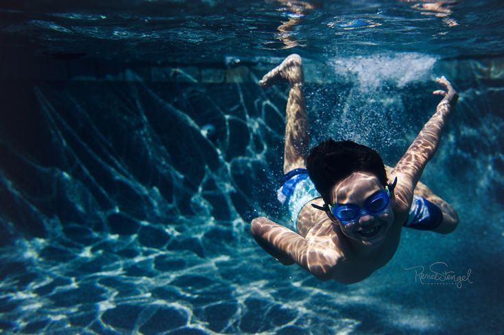 Underwater photo of boy diving into the pool in goggles by RENEE STENGEL Photogr...