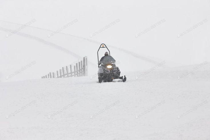 Snowmobile on the snow. White winter mountain landscape. Horizontal By ABBPhoto...
