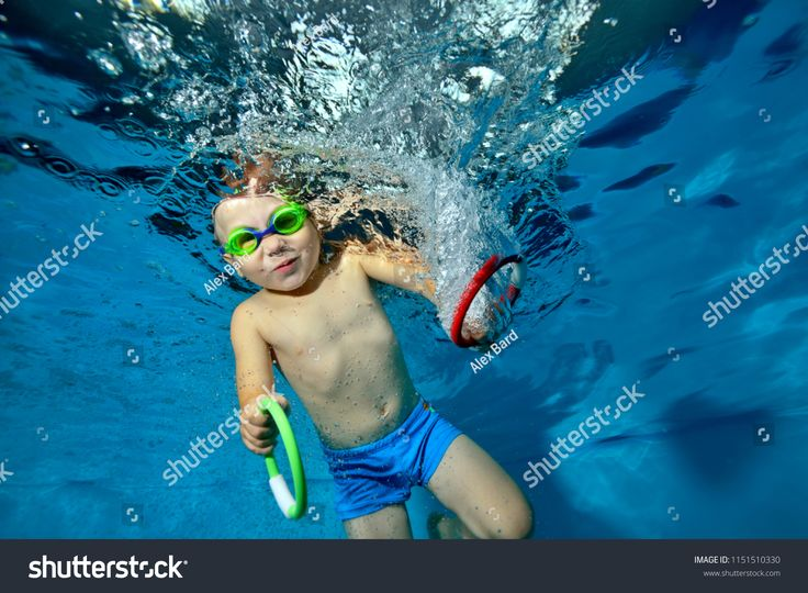 Happy kid doing sports and swimming underwater in the pool on a blue background ...