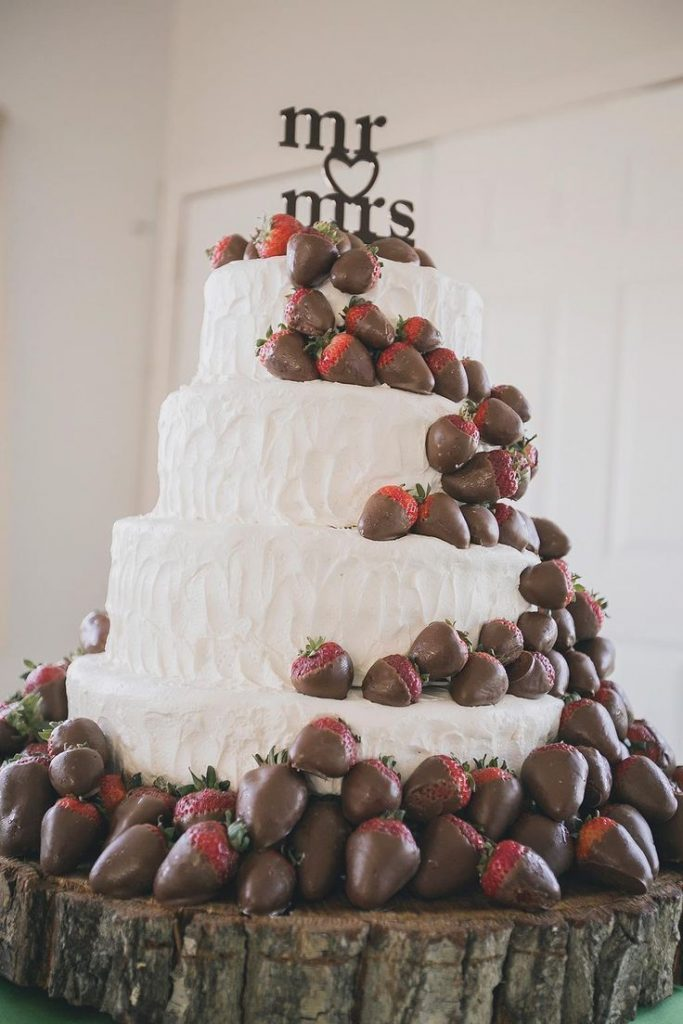 This white wedding cake topped with chocolate covered strawberries is the stuff ...